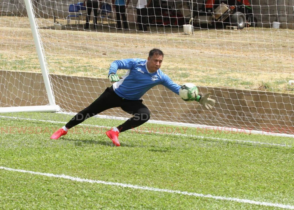 Commissioner of Police Gary Griffith tries to save an attempt by Terry Fenwick during the opening of the refurbished police football grounds on Long Circular Road, St James, on Friday. PHOTO BY AYANNA KINSALE - Ayanna Kinsale