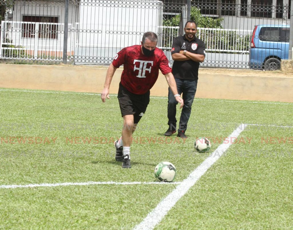Terry Fenwick takes a shot at goal, against Commissioner of Police Gary Griffith, during the opening of the refurbished Police football ground at Long Circular Road, St James on Friday. PHOTO BY AYANNA KINSALE. - Ayanna Kinsale