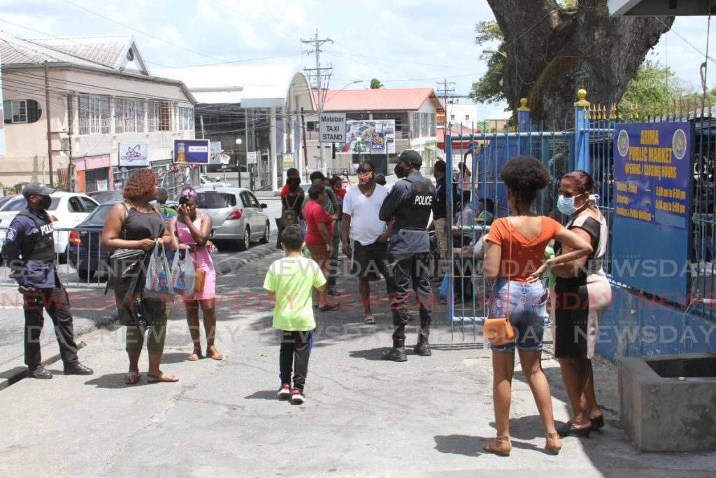 Police officers ensure shoppers do not enter the Arima Market on Saturday after it was temporarily closed to remove a batch of poisoned ginger. - Angelo Marcelle
