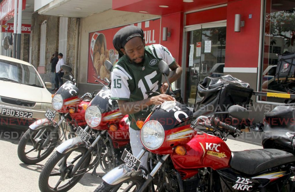 GETTING READY: This KFC worker sanitises a motorcyle at the Independence Square, Port of Spain branch on Sunday.   - Ayanna Kinsale