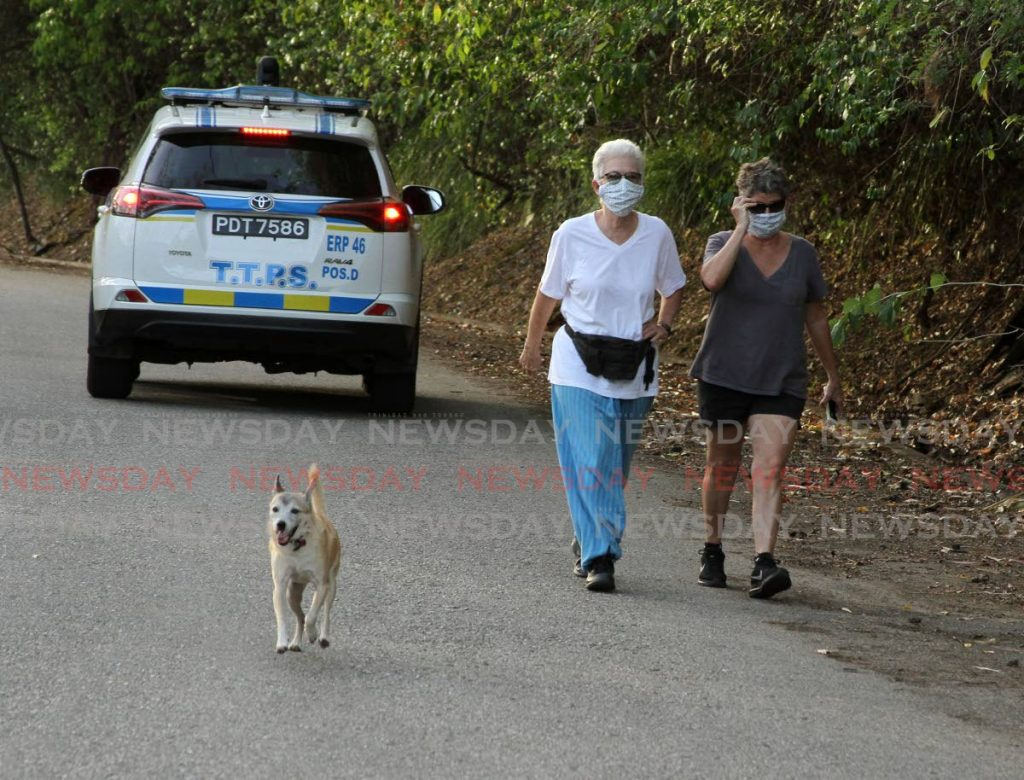 Two women take a walk, while police were on patrol, on Lady Chancellor Hill, St Ann's, last Tuesday. PHOTO BY AYANNA KINSALE -