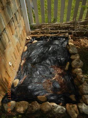 Preparing the compost area with polyethylene anchored with boulders. -