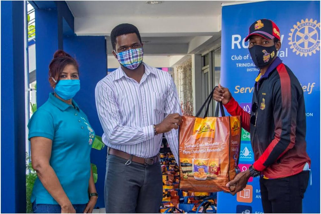 Rotary Club of Maraval president, Marcia Prince-Assam, left, Rainbow Rescue representative Kirwin Samuel and and Trinbago Knight Riders spinner Khary Pierre at the Rotary's hamper drive.  -