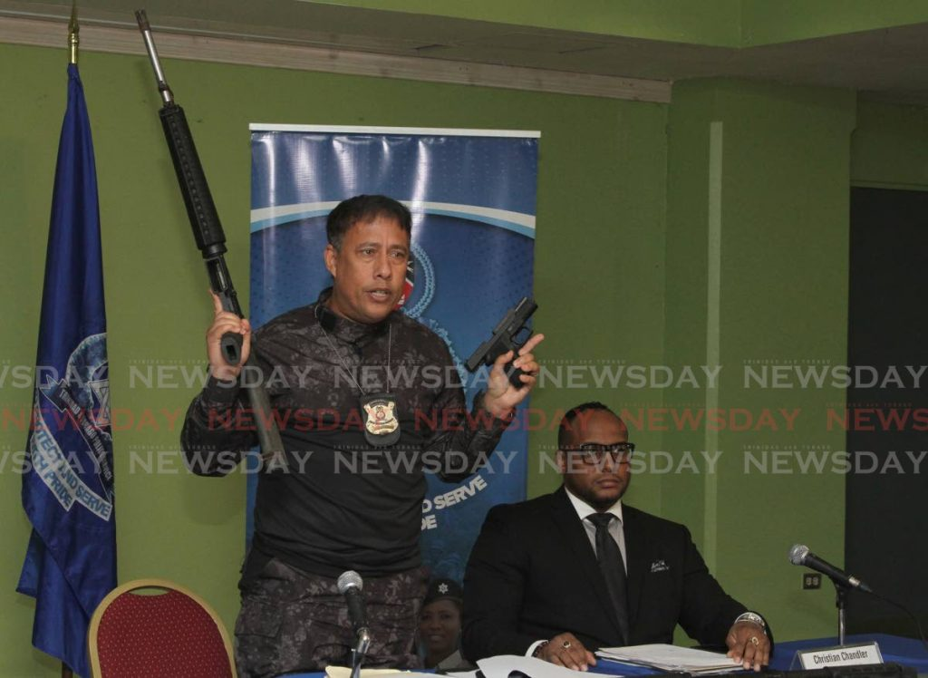 GARY'S GUNTALK: Police Commissioner Gary Griffith displays firearms during a press conference on Monday at Police Administration Building in Port of Spain. At right is Head of the police's legal unit,  Christian Chandler.  PHOTO BY AYANNA KINSALE - Ayanna Kinsale