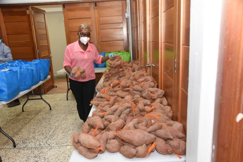 A volunteer assorts sweet potatoes to be packed in food hampers for distribution across TT through food banks set up by BPTT and the Rose Foundation.   -