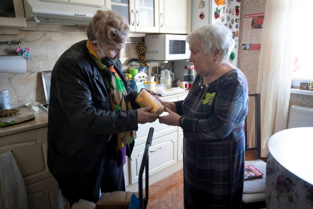 In this photo taken on Thursday, April 30, 2020, Galina Yakovleva, left, gives charity food to Lyubov Travkina, 83 in her apartment in St Petersburg, Russia. Every day amid the coronavirus pandemic, 80-year-old Leningrad siege survivor Galina Yakovleva has driven to the city in her white minivan to bring charity groceries and goods to elderly people and families with children in need.  - AP PHOTO