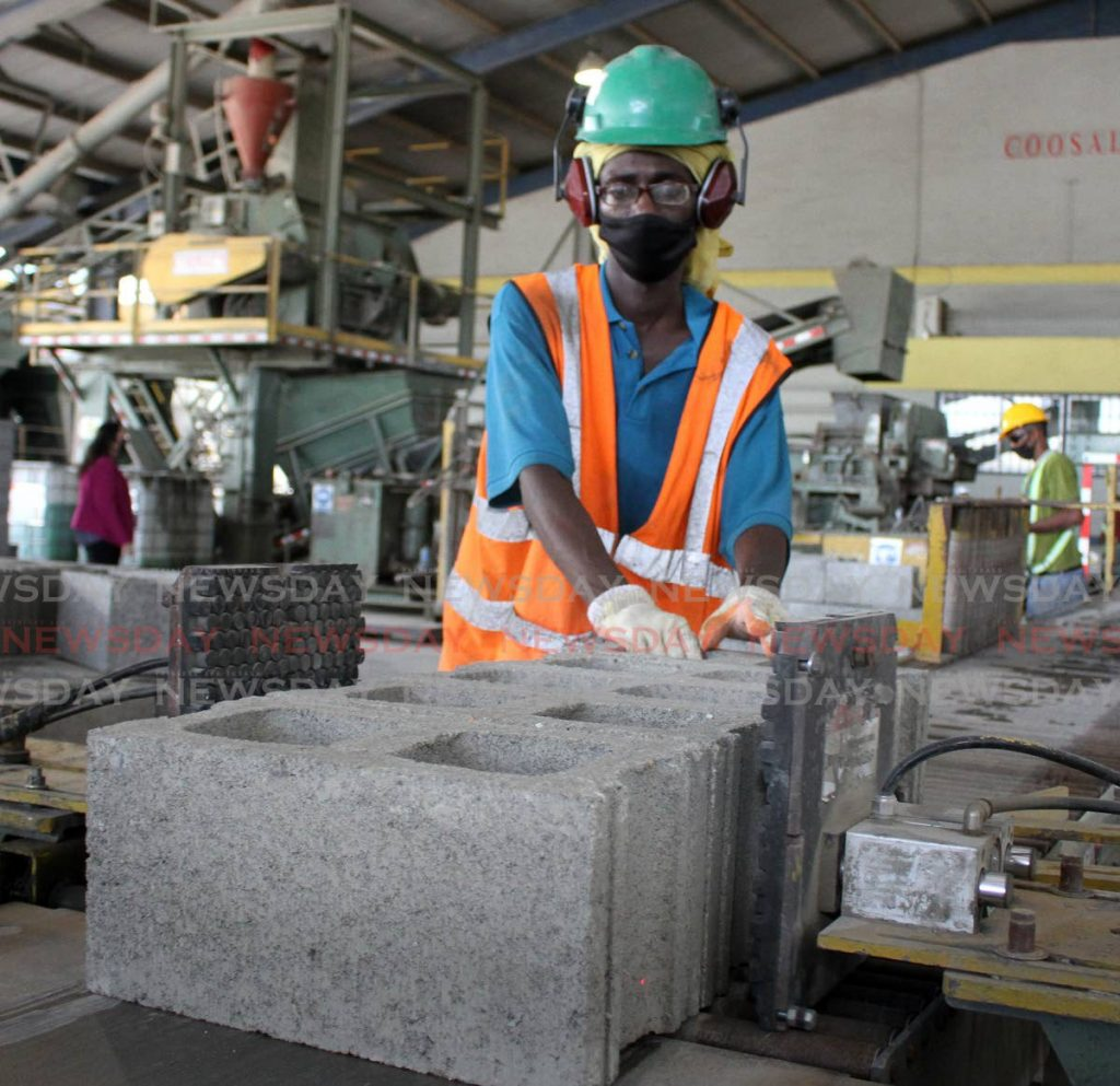 An employee of Coosal's Construction Company Ltd, pinches blocks on a conveyance belt, at the company's Madras Settlement Road, Chin Chin, Cunupia, manufacturing site on Thursday. - ANGELO MARCELLE