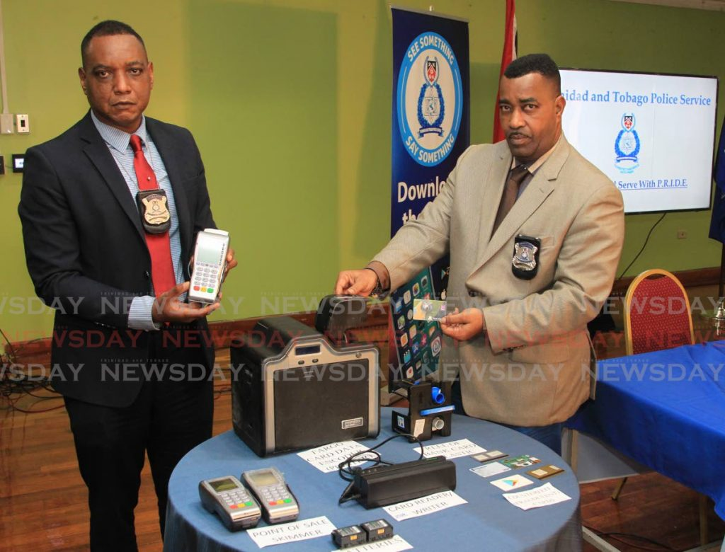 ASP Curtis Julien (right) and Inspector Cornelius Samuel, officers attached to the Fraud Squad Division of the TTPS, show how fraudsters harvest bank card information during point of sale transactions. - ROGER JACOB