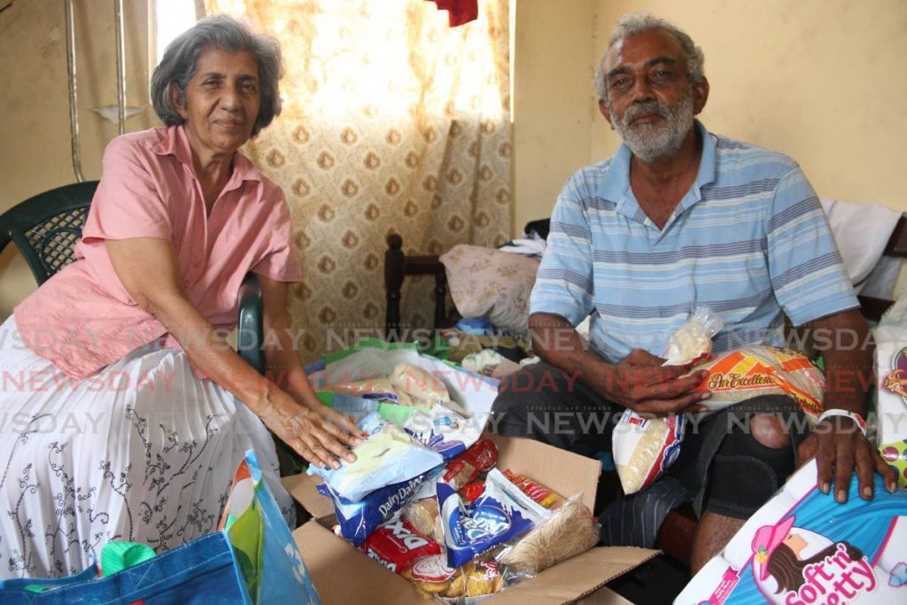 GIVING BACK: Evans Rajpaul and his wife Vitra Teelucksingh-Rajpaul package foodstuff, which they received from caring members of the public, to distribute to others who are also in need.   PHOTO BY MARVIN HAMILTON -