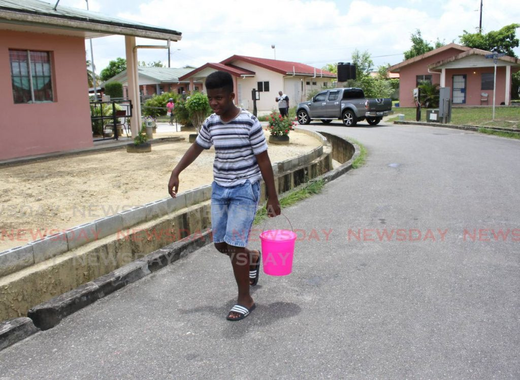 Tyrese Mc Millan takes a bucket of water to his home in a three-floor apartment in phase three Greenvale Park, La Horquetta. -