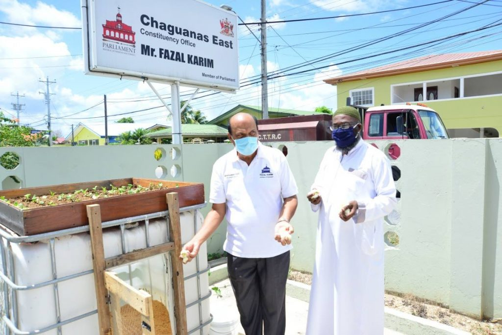 Chaguanas East MP Fazal Karim and a member of a religious organisation examine a grow box in the constituency's food sustainability drive last Thursday. Photo courtesy Chaguanas East constituency.  -