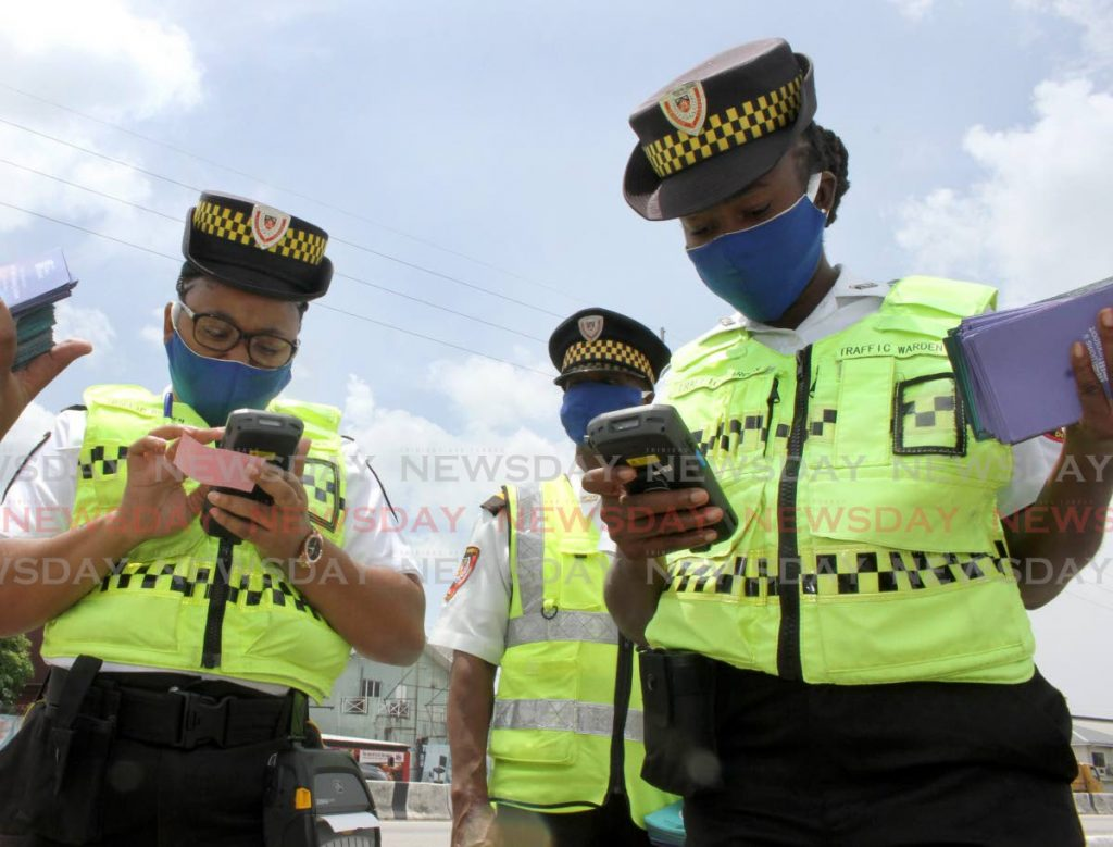 File photo: Traffic wardens check out their handheld ticketing devices at the launch of the demerit point and traffic ticketing system on the Audrey Jeffers Highway in Port of Spain in May. Photo by Angelo Marcelle
