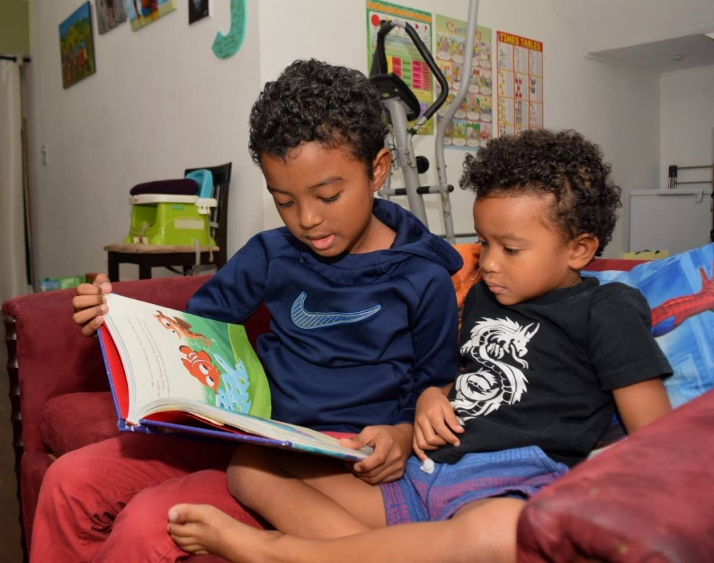 Jean-Michael Woodroffe reads to his brother Jaden at their home in Maracas, St Joseph. -