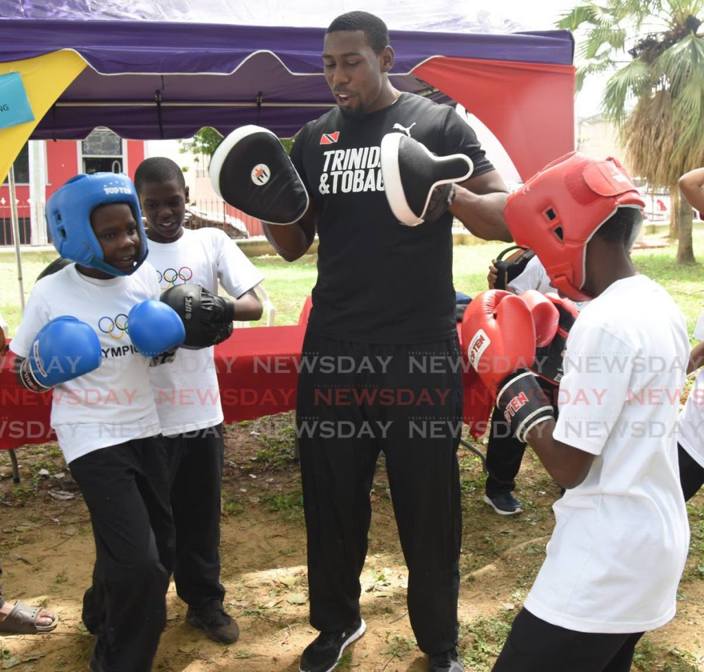 In this June 21, 2019 file photo, TT boxer Nigel Paul teaches boxing techniques to two boys during Olympic Day 2019 at Lord Harris Square, Port of Spain. -