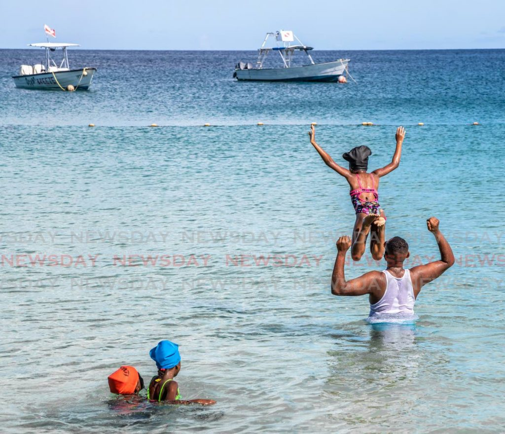 In this July 2019 file photo a family enjoys a day at Store Bay, Tobago. Beaches, rivers reopen to the public on Monday, the Prime Minister announced on Saturday. - JEFF K MAYERS