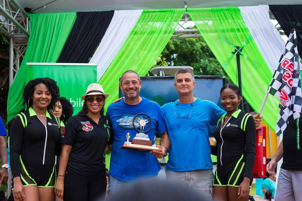 In this Aug 17, 2019 file photo, bmobile brand representatives and TSTT's Enterprise Marketing Manager, Siobhan Thompson, celebrate with champs Sheldon Edghill (driver) and Anthony Brash (throttleman) of team Energiza, at the 51st Great Race, in Store Bay, Tobago. (Photo courtesy bmobile) -