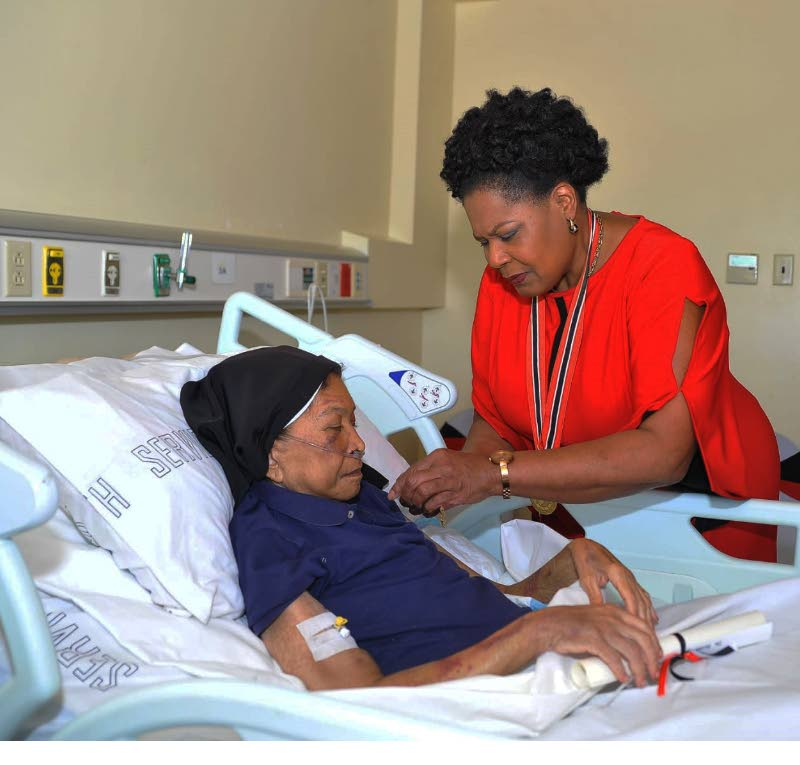 FILE PHOTO: President Paula-Mae Weekes pins the Medal of Merit (Gold) on the garment of Dr Sister Phyllis Warfe on September 27, 2019, at the Scarborough General Hospital in Tobago. PHOTO COURTESY OFFICE OF THE PRESIDENT -