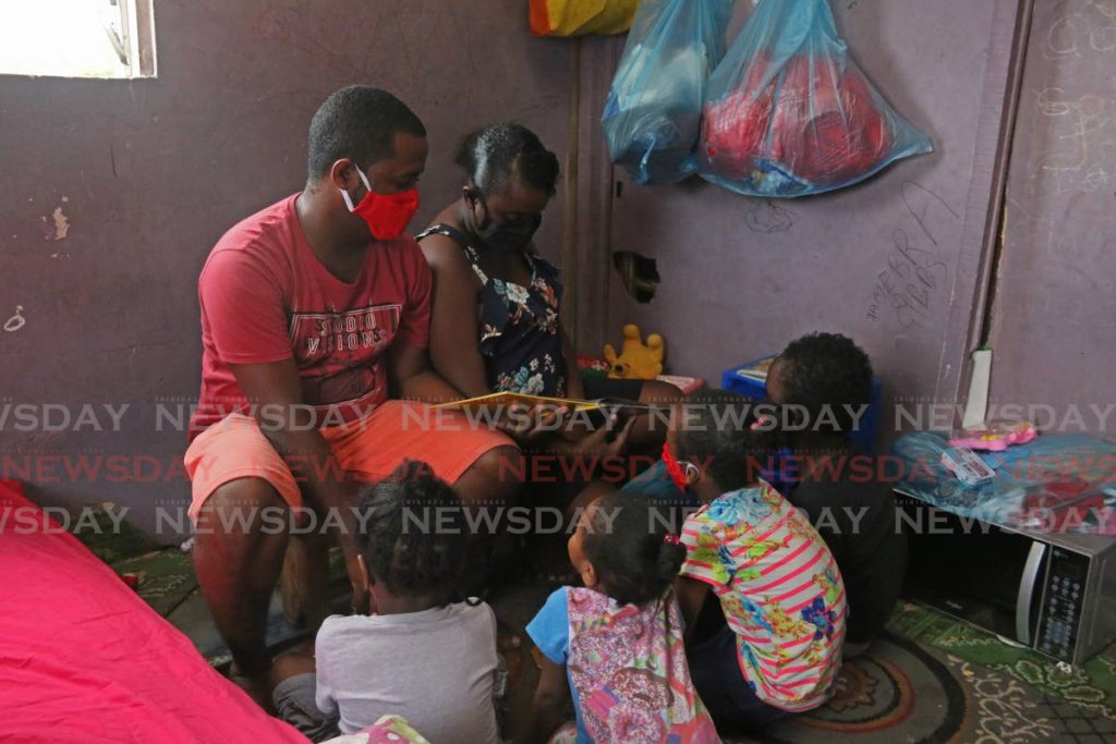 FILE PHOTO: Marcus Gibbs, left, and his wife Tamerra David read a story book to their four children at an abandoned house on Germain Avenue, Petit Bourg, on April 21. - Marvin Hamilton