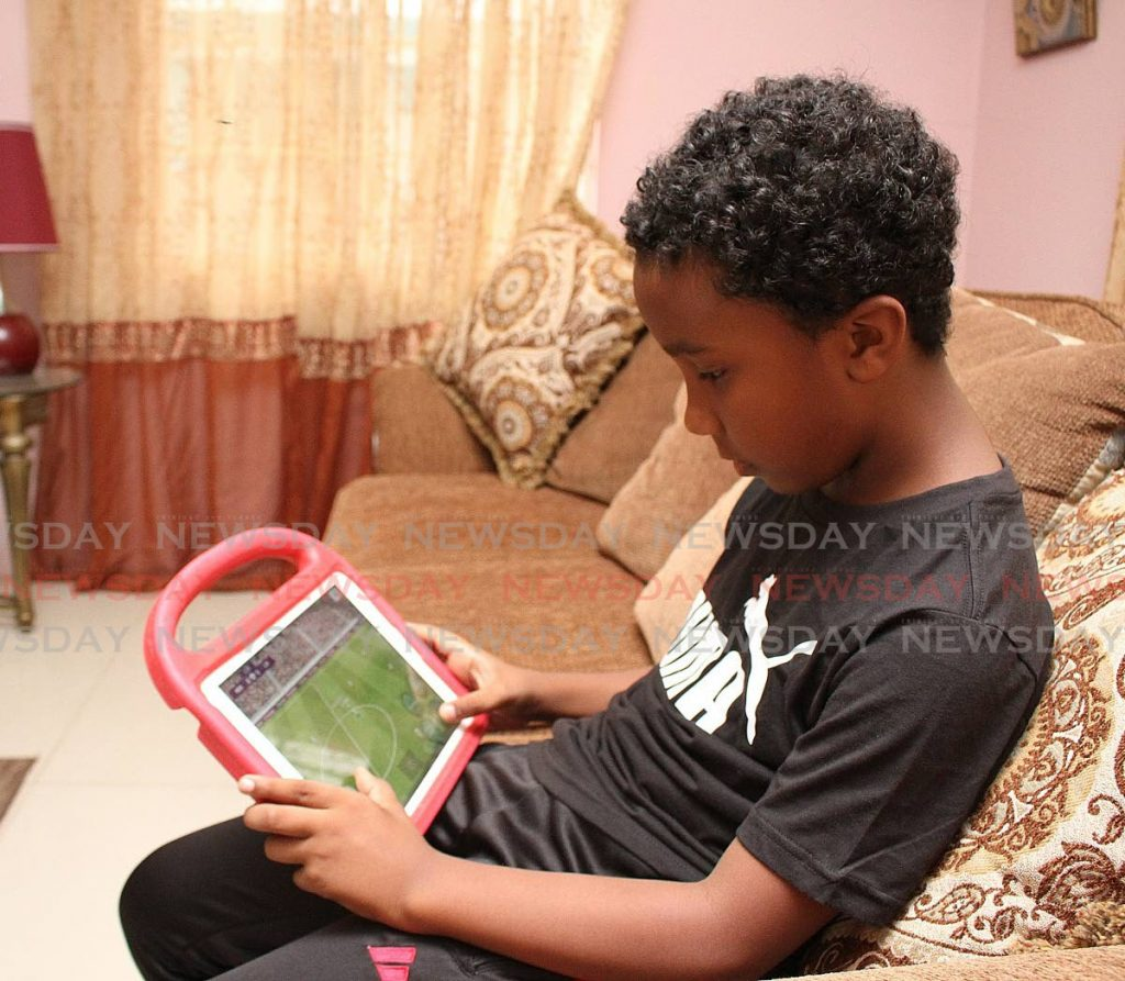 Kymani Dematas relaxes by playing a football game on his tablet at home in Santa Rosa Heights, Arima. -