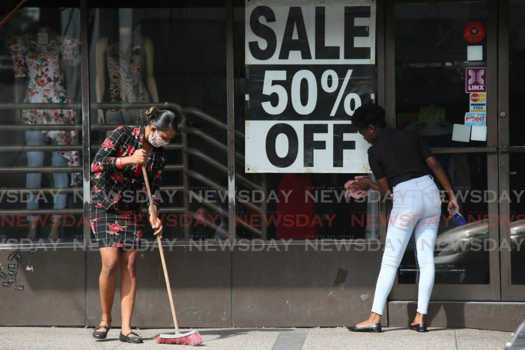 Employees clean a store on High Street, San Fernando which offers a 50 per cent off sale after the reopening of the retail sector on June 1. PHOTO BY LINCOLN HOLDER -