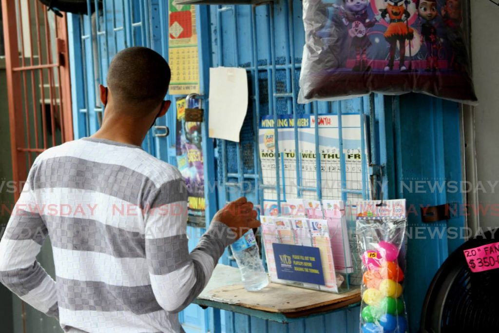 A man makes his picks at a NLCB booth in Arima on June 1 when outlets reopened. - Angelo Marcelle