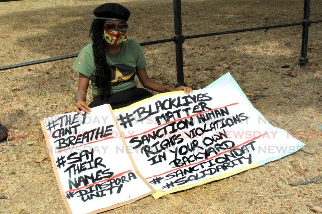 In this June 4 file photo Abeo Jackson sits on the grass at the Queen's Park Savannah, Port of Spain, opposite the US embassy with posters protesting the killing of George Floyd and other black people in the US.  - ROGER JACOB