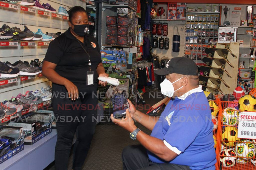 Lorraine Ramdhan, manager of the Long Circular Mall branch of Sports and Games, helps Cecil Thomas choose a pair of sneakers on June 1. While there is no legal requirement to wear masks, it is a significant part of the guidelines for the reopening of businesses, facilities and institutions established and released by the Ministry of Health. - Ayanna Kinsale