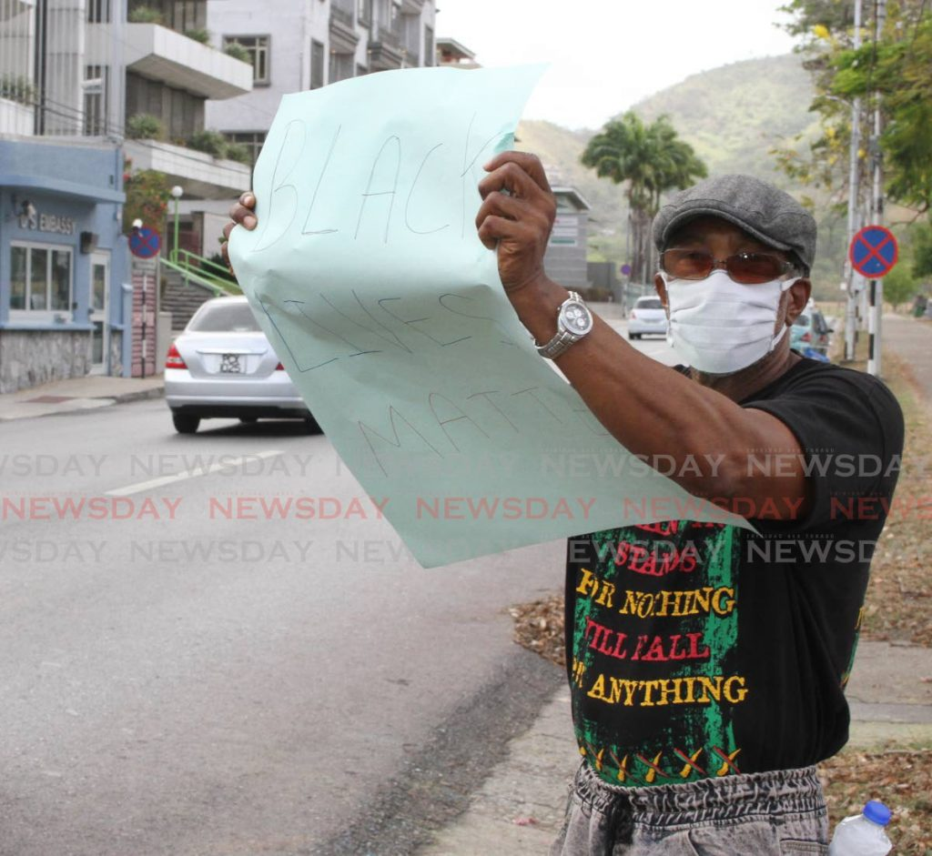 In this June 5 file photo an MSJ activist shows solidarity with the Black Lives Matter movement protesters in the US, by displaying a Black Lives Matter placard opposite the US Embassy, Queen's Park Savannah, Port of Spain, on Wednesday.  The MSJ organised the event.  - Angelo Marcelle