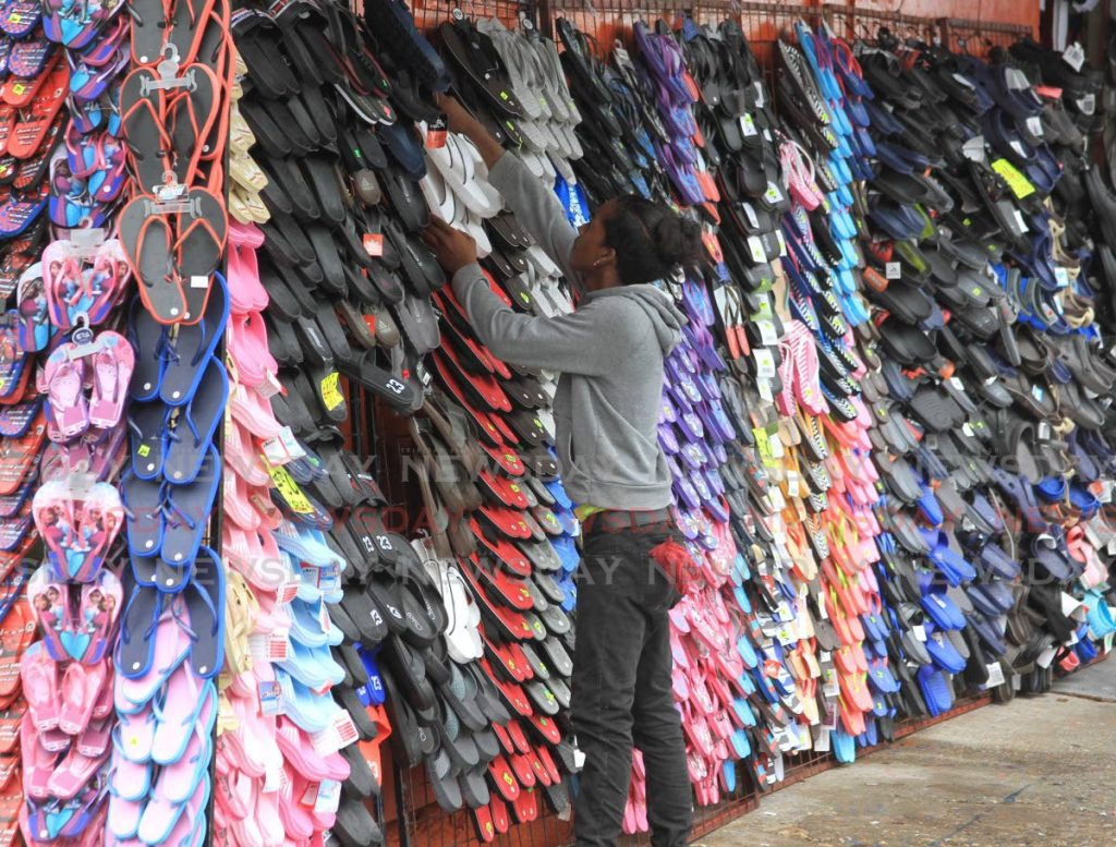 An employee adjusts goods on display at at the Tunapuna Retail and Bargain Corner on Saturday. - Ayanna Kinsale