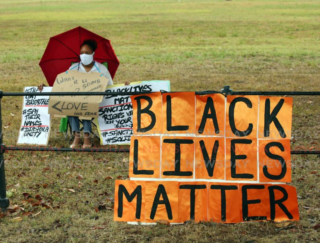 A protester sits among signs in support of the Black Lives Matter movement at the Queen's Park Savannah, opposite the US , Port of Spain on Friday. PHOTO BY SUREASH CHOLAI -