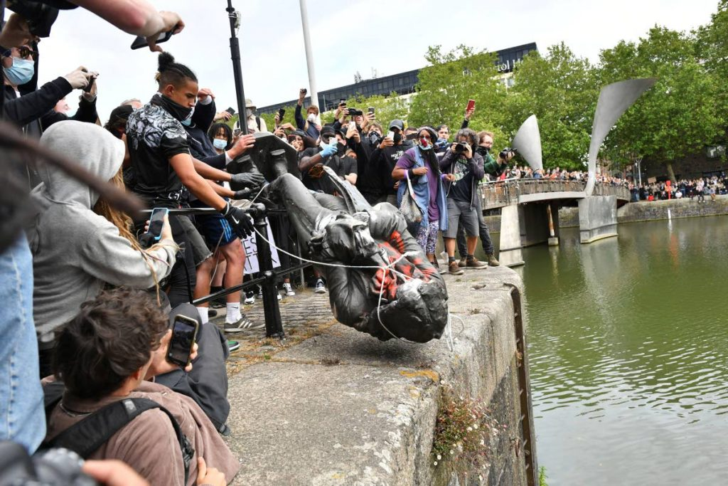 Protesters throw a statue of slave trader Edward Colston into Bristol harbour, during a Black Lives Matter protest rally, in Bristol, England, on June 7, 2020, in response to the recent killing of George Floyd by police officers in Minneapolis, USA, that has led to protests in many countries and across the US. - AP PHOTO