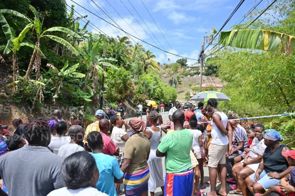 Scores of people gather at the scene of the accident which took the life of hardware owner Curtis Phillips on Sunday. PHOTO BY LEEANDRO NORAY -