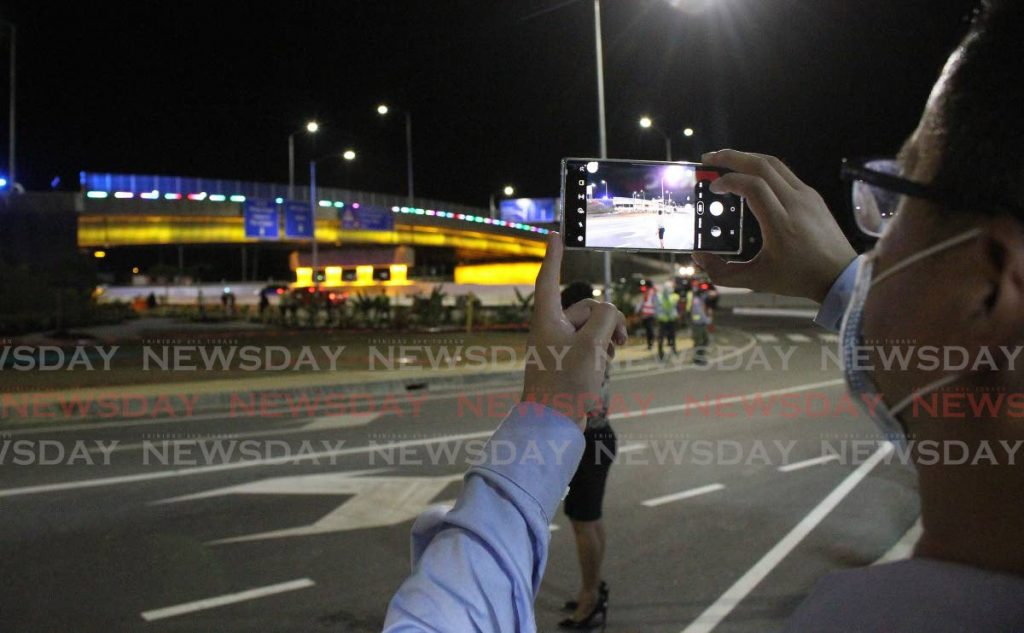 A man takes a photo of the newly completed and lit Curepe interchange, Churchill Roosevelt Highway on Monday evening. - Angelo M. Marcelle
