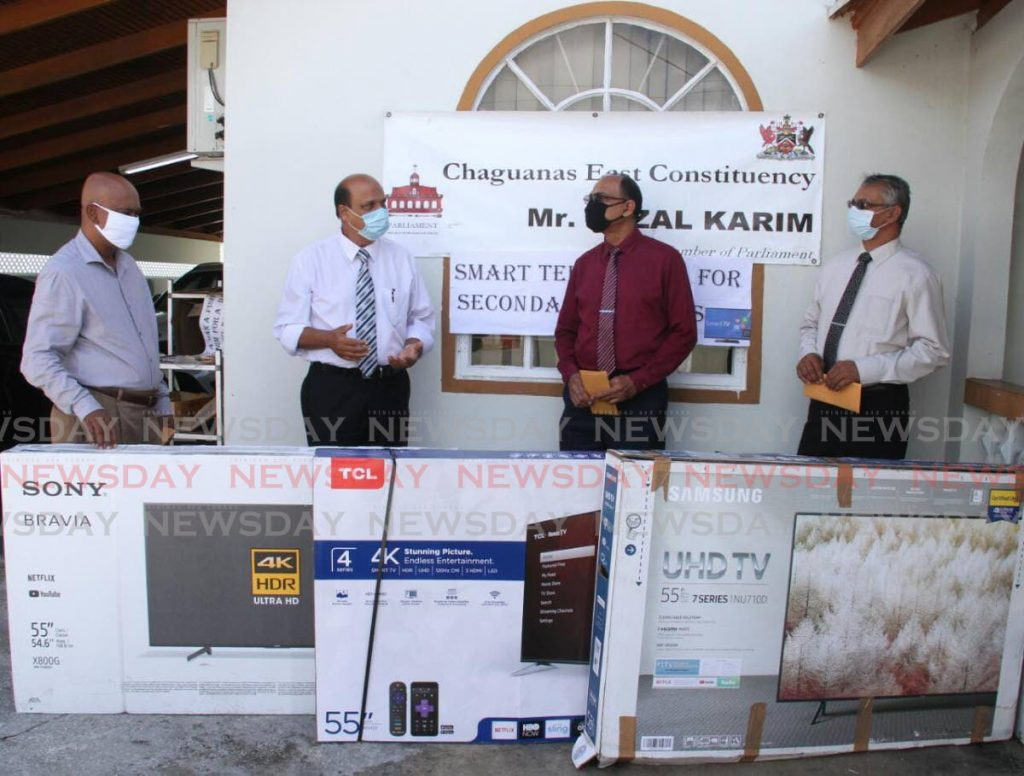 HELPING HAND: Chaguanas MP Fazal Karim, 2nd from left, with the smart televisions which he donated on Monday to three schools within his constituency. Also in photo from left are principals Kelly Birjur (Chaguanas North Sec), Bharat Maharaj (Chaguanas South Sec) and Lochan Harrichan of  Cunupia Secondary. PHOTO COURTESY CHAGUANAS EAST CONSTITUENCY OFFICE - Chaguanas East Constituency Office