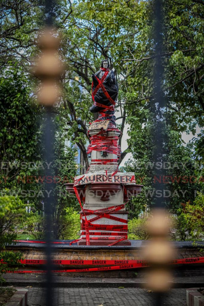 DEFACED: The defaced statue of Christopher Columbus is seen through the locked gates of its square in East Port of Spain on Monday.   - JEFF K MAYERS