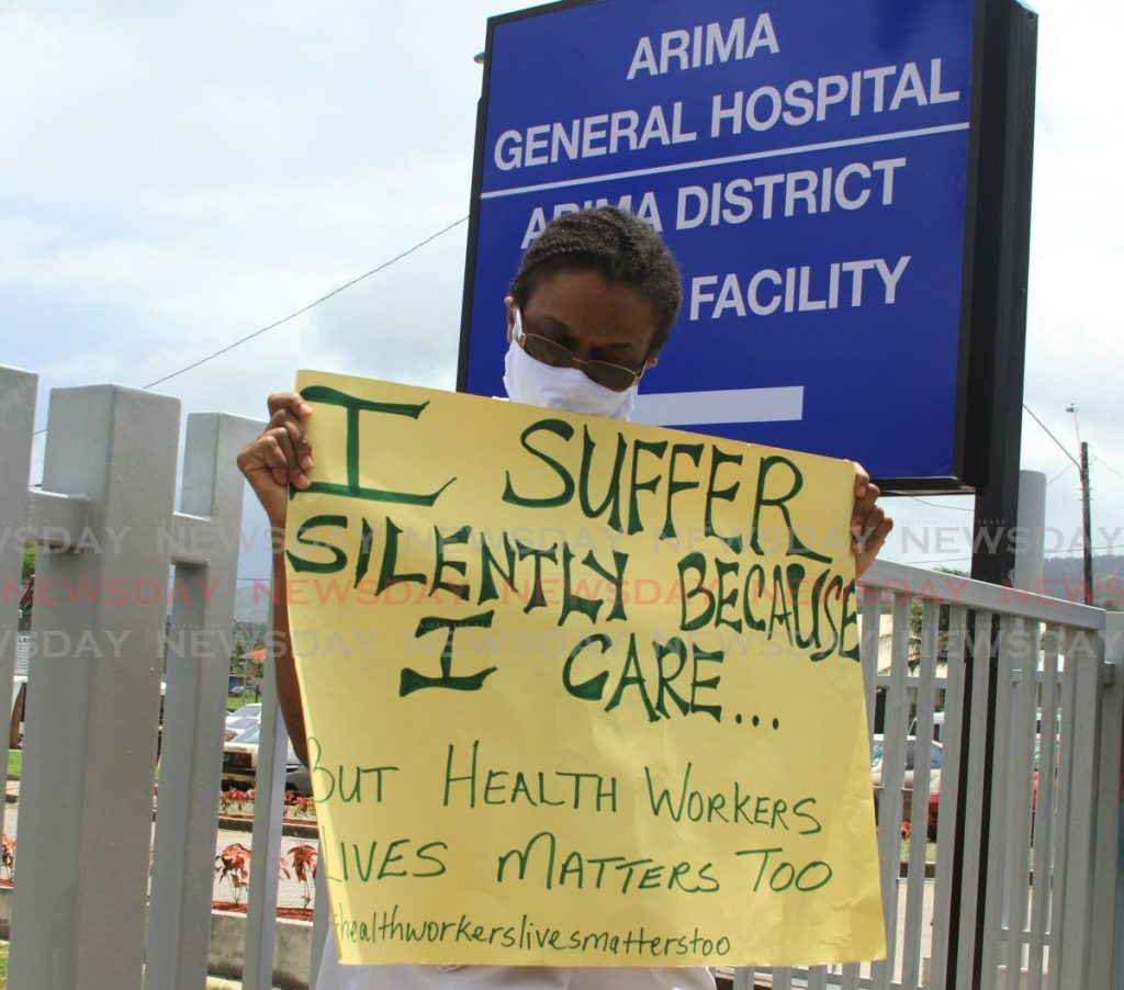A nurse reads her placard during a protest at the Arima General Hospital on Monday. - Ayanna Kinsale