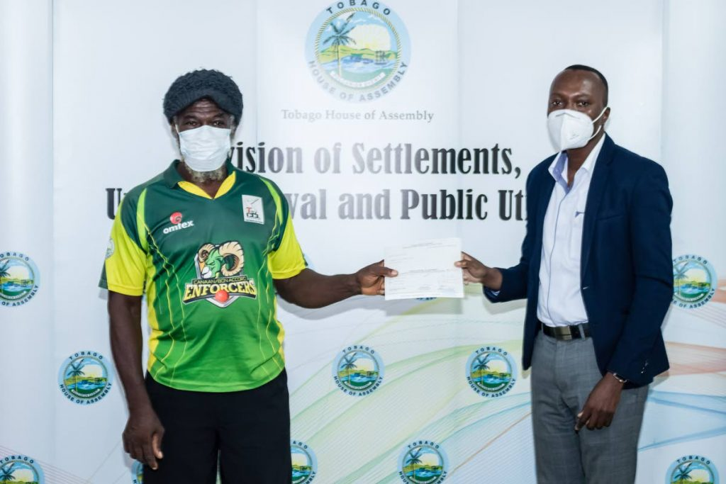 Chief Secretary Honourable Ancil Dennis presents Mr. Anthony Boyce with his second tranche cheque valued at TT$10,000.00  for the Home Completion Programme at the Division of Settlements, Urban Renewal and Public Utilities last Friday.  - THA PHOTOS
