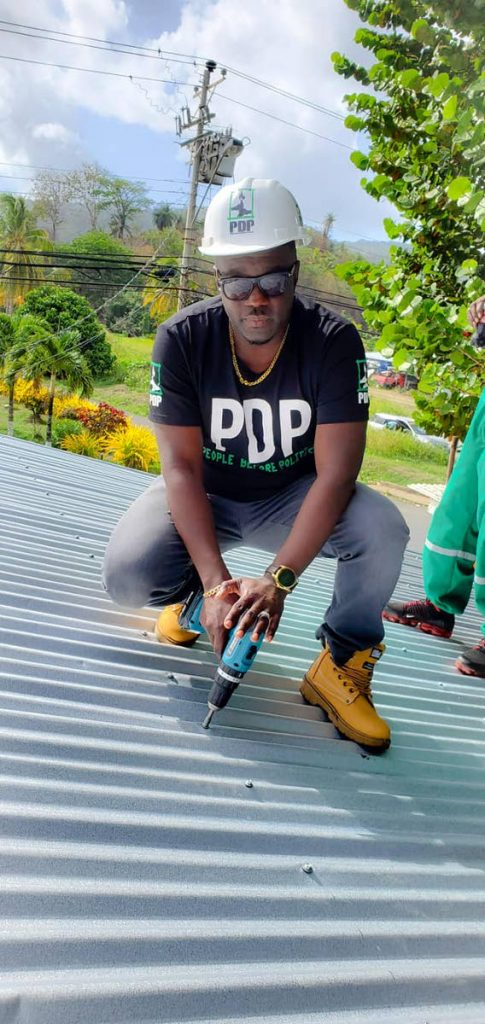 PDP leader Watson Duke uses a power screwdriver to fasten bolts to galvanised sheets on a house. -