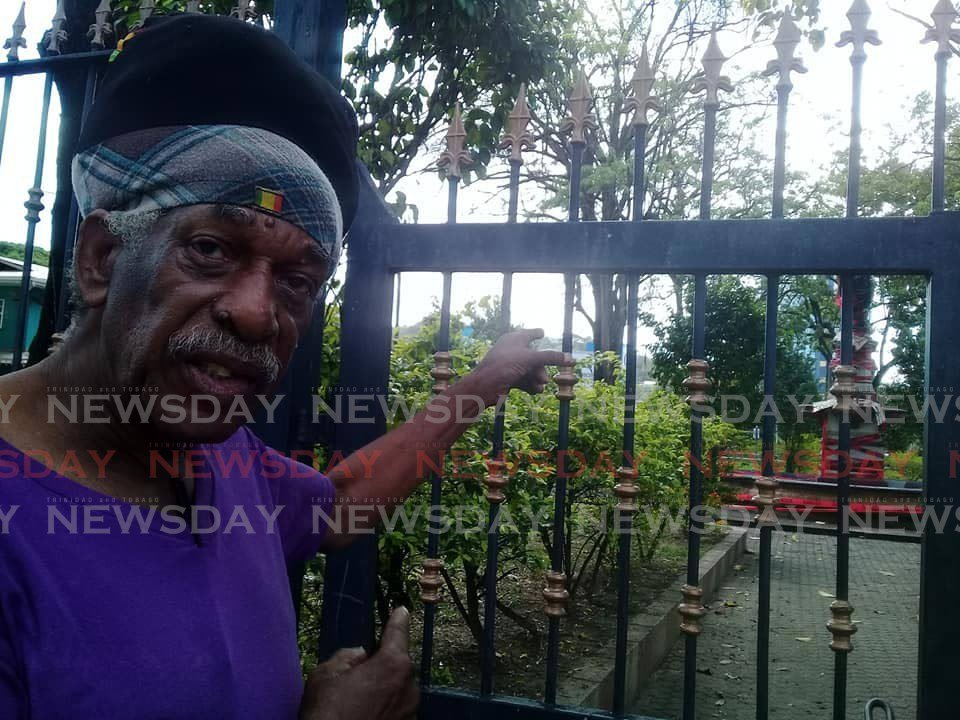 Keith Pierre, 80, points at the statue of Christopher Columbus in downtown Port of Spain, saying he would like to see the statue removed and better taken to the park for residents to enjoy.   - Shane Superville