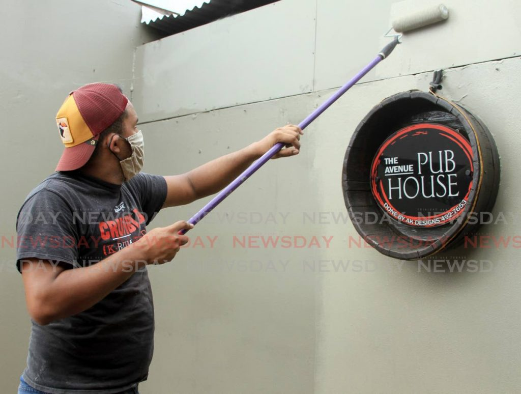 Luiz Hernandez applies a fresh coat of paint at The Avenue Pub House ahead of the reopening on Monday. - Ayanna Kinsale