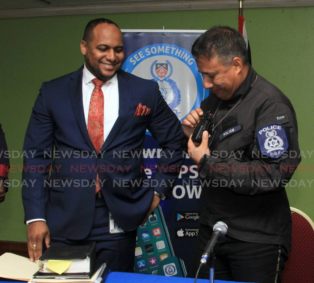 Christian Chandler, left, head of the TTPS legal unit, looks on as Police Commissioner Gary Griffith shows how a body camera is attached to an officer's uniform during a press briefing at Police Administration Building, Port of Spain on June 18.  - Ayanna Kinsale