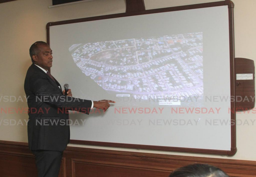 HDC managing director Brent Lyons points to a map showing the piece of land which was cleared in Wallerfield on Friday last week.  PHOTO BY AYANNA KINSALE -
