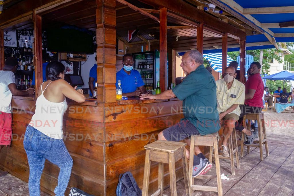 Patrons, some wearning masks, enjoy a drink at Anchors bar at Mt Irvine, Tobago on June 22. Government on Saturday warned bars they will be closed if patrons do not practise social distancing as set out in the covid19 guidelines. - DAVID REID
