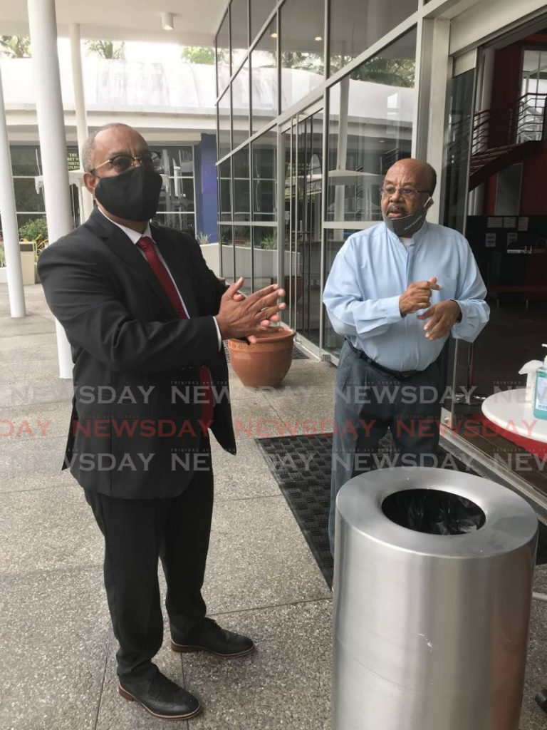 SOMEONE OLD, SOMEONE NEW: New PNM candidate for La Brea attorney Steve McLatchie (left) sanitises his hands before entering Queen's Hall, St Ann's to be screened. Looking on is former La Brea MP Hedwige Bereaux.   PHOTO BY JULIEN NEAVES - Julien Neaves