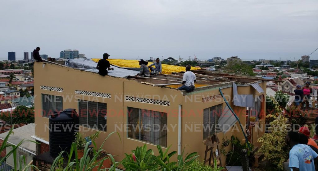 File photo: Volunteers help secure a tarpaulin on the roof of Glenda Cuffie at Layann Hill, Belmont after her roof was ripped off by strong winds on Saturday. - ROGER JACOB