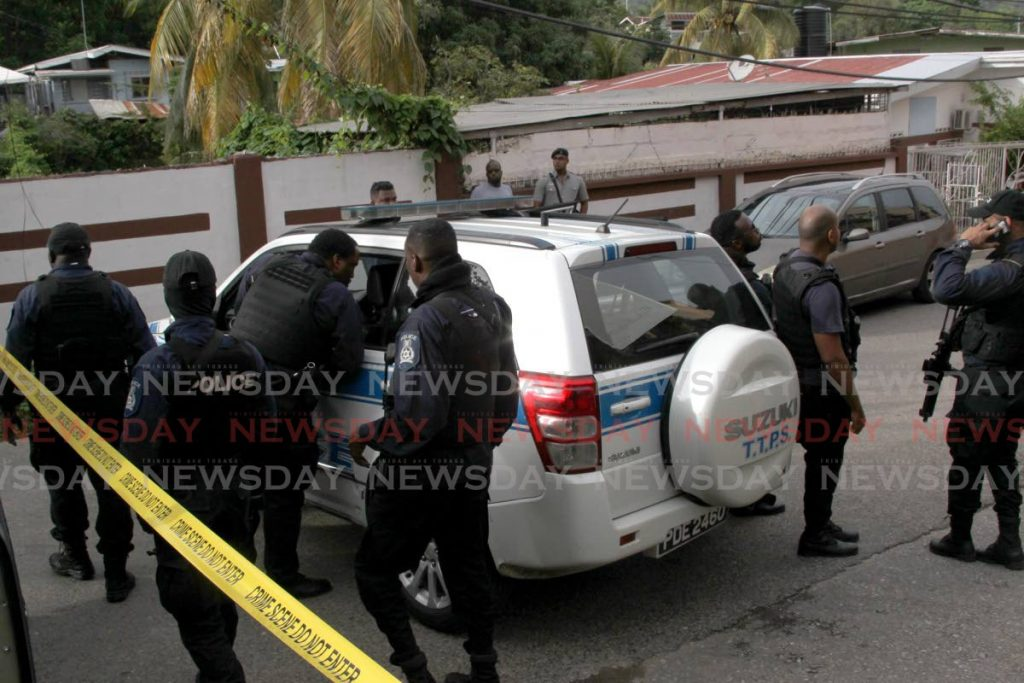 Some of the officers who were at the scene of the fatal triple shooting in Morvant on Saturday. - ROGER JACOB