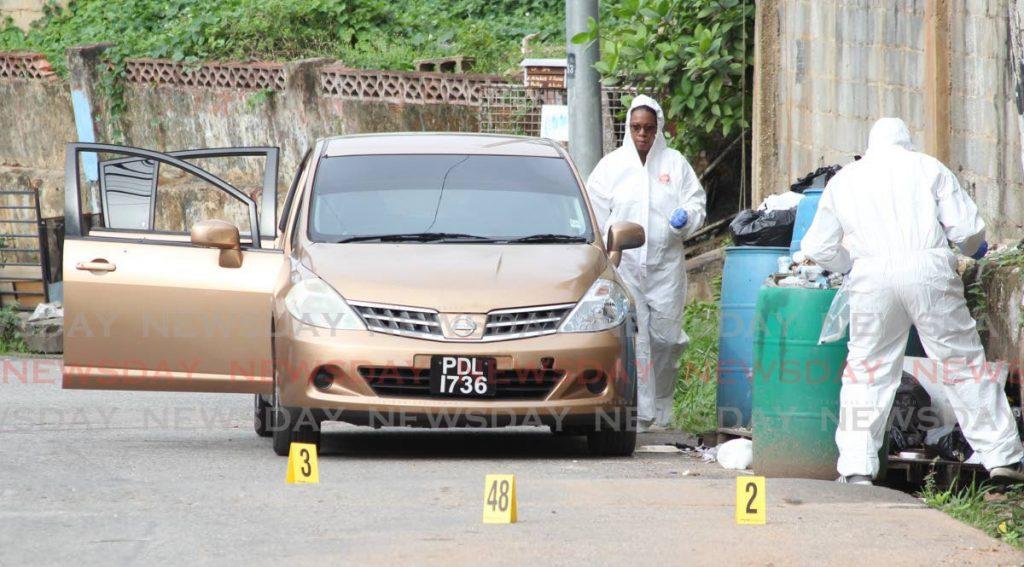 Crime Scene investigators gather clues at the scene where three men were shot dead by police in Morvant on Saturday. - ROGER JACOB