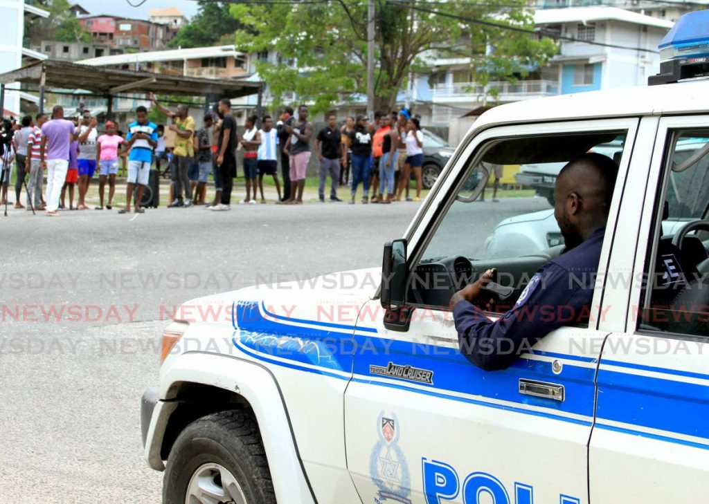 A police officer looks on as Morvant residents protest after three men were killed by the police in the area on Saturday. - Ayanna Kinsale