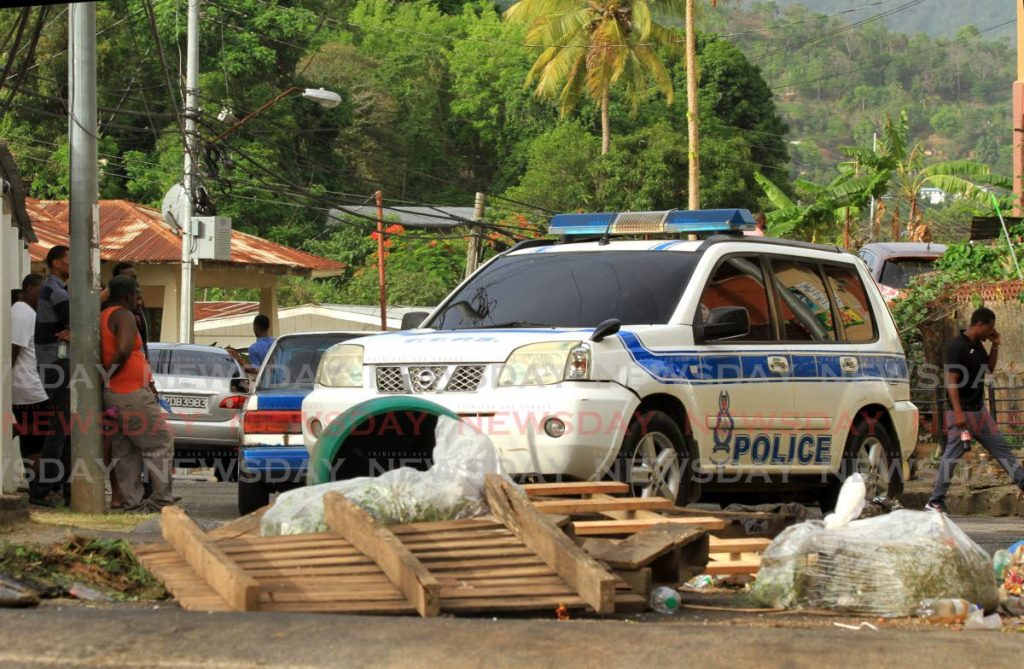 A police vehicle returns to Juman Drive, Morvant, on Monday after residents blocked the road with debris for a second time to protest the killing of three men by police on Saturday. - Ayanna Kinsale