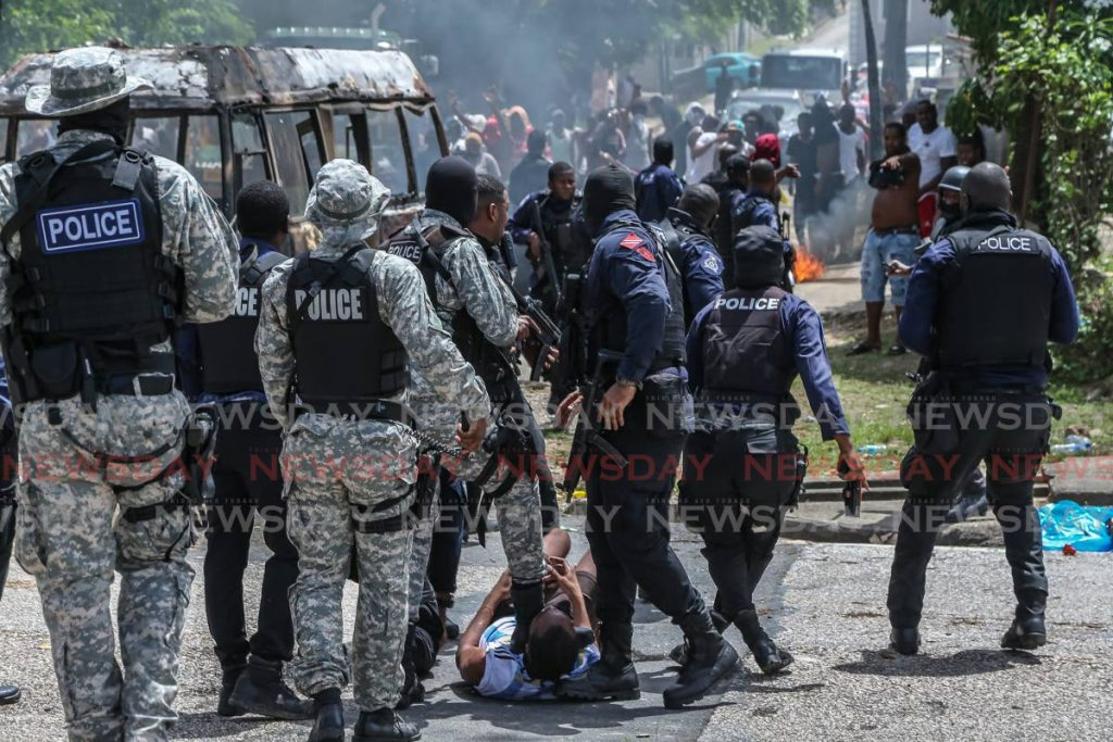 A police officer can be seen using his foot to immobilize a protester during today's fiery demonstrations in east Port of Spain - Jeff Mayers